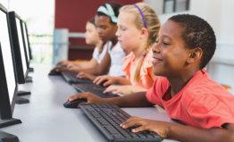 School kids using computer in classroom
